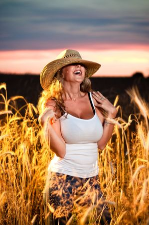 An attractive young woman in a straw hat standing in a filed of wheat at sunset, laughing hard