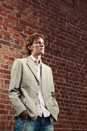 A handsome young man in a light-coloured suit posed against a brick wall, looking contempative
