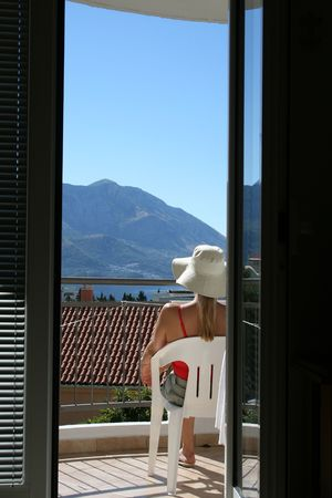 Young lady enjoying the sun on the balcony of her hotel room. View from behind, with blue skies and mountains in the background photo