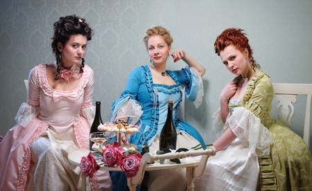aristocracy: Three beautiful ladies in lavish dresses in a historical setting Stock Photo