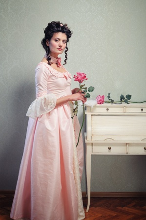 historical clothing: A young brunette lady in a pink ancient dress holding a rose
