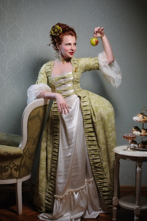 aristocracy: Red-haired lady in a green historical dress is holding an apple Stock Photo