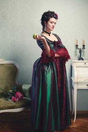 aristocracy: Beautiful brunette in a historical dress posing with an apple in her hand