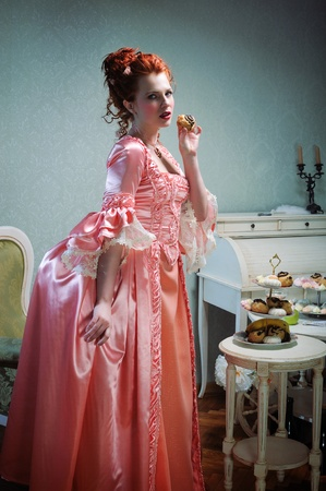 ancients: A gorgeous red-haired lady in a lavish ancients dress holding a cake Stock Photo