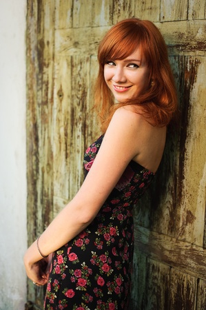 A  young beautiful red-haired girl with a sly smile. Shot against an old textured green door.