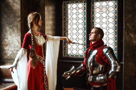 awarded: A young squire being awarded knighthood by a noble lady.
