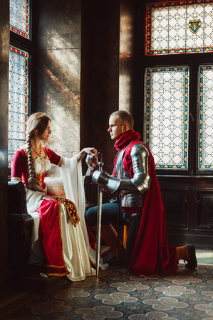 A young knight kneels down before his lady to pronounce his engagement vow. Stockfoto