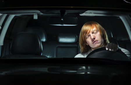 driving: A young man exhausted and falling asleep while driving his car at night