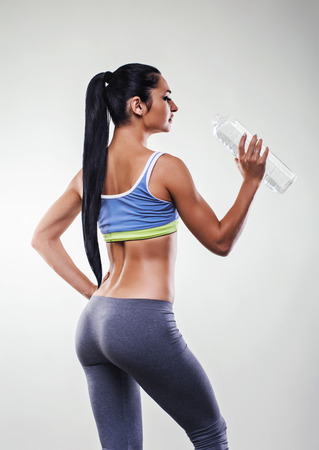 Young athletic woman is about to drink water after a workout.