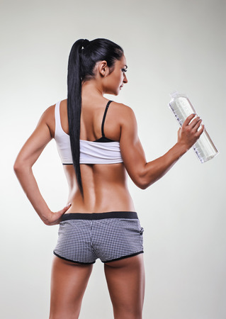 Young athletic woman preparing to drink some water after a workout.
