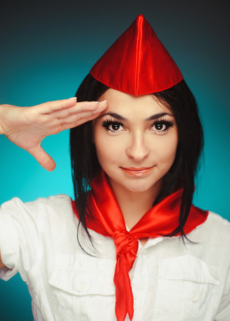Attractive young brunette dressed as a member of the Young Pioneer saluting.