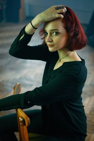 A beautiful red-haired girl looking boldly at the viewer. Stockfoto