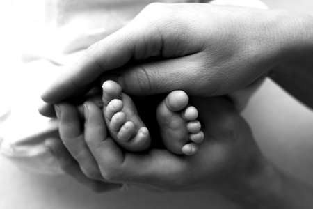 Feet of a newborn in the hands of a father, parent. Studio photography, black and white. Happy family concept.