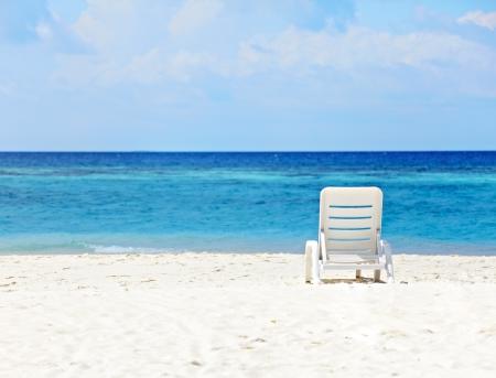 strandstoel: Witte dek-stoel staande op het strand van de blauwe oceaan
