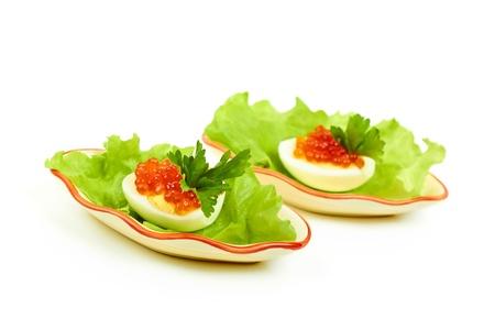 ensalada rusa: huevos con caviar rojo en una hoja de lechuga