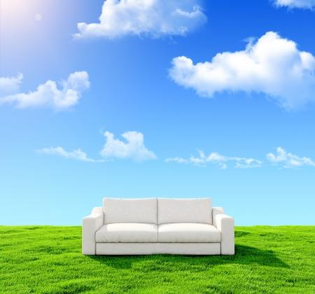 白いソファの青い空を背景に緑の野原 写真素材
