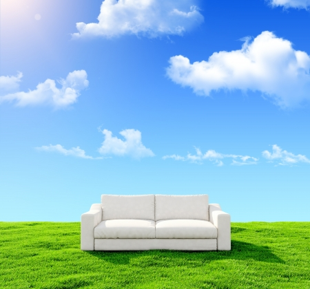 green couch: White sofa on a green field against the blue sky