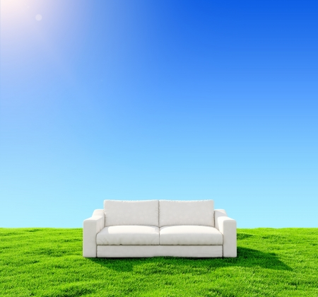 White sofa on a green field against the blue sky photo