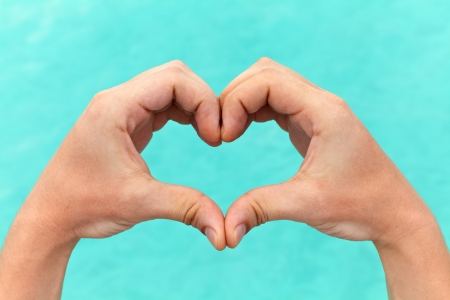Hands in the shape of a heart against a blue lagoon photo