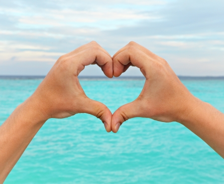 Hands in the shape of a heart on a background of blue sea photo