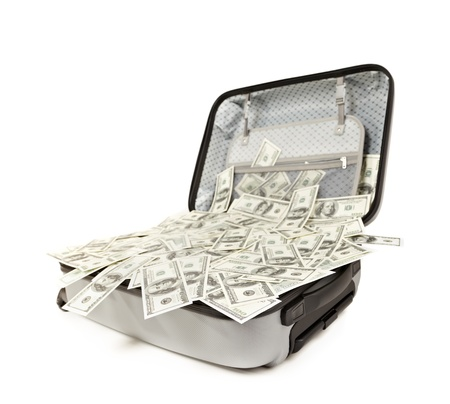 lot of money in a opened suitcase isolated on white photo
