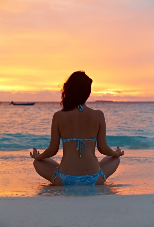 Woman meditating on the beach at sunset in the sea photo