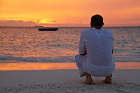 A man in a white shirt sitting on the background of a beautiful sunset in the sea photo