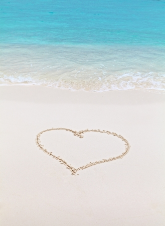 Heart drawn on sand on the beach photo