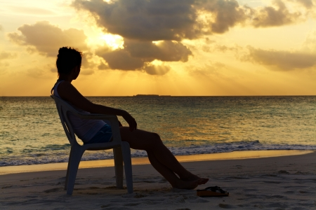 Silhouette of a girl on a chair against a beautiful sunset in the ocean, Maldives photo