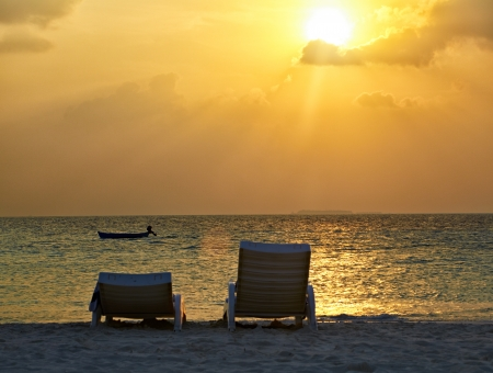 Two chaise lounges at sunset in the sea photo