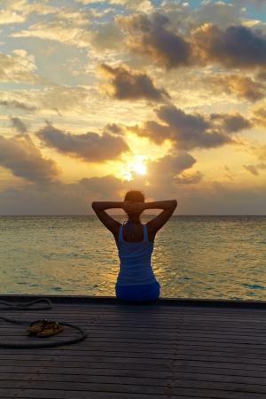 chica surf: ni�a sentada en un muelle en contra de una hermosa puesta de sol en el mar Foto de archivo