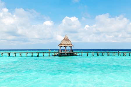A wooden arbor on the water in the lagoon  Bright symmetrical water landscape of the Maldives photo