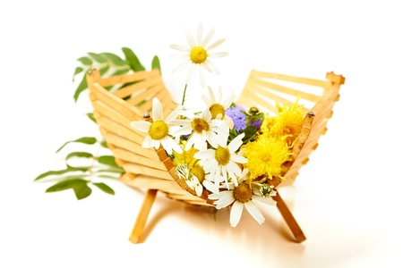 wild flowers in a wooden basket on a white background photo