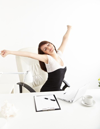 the yawn: businesswoman stretching at her workplace