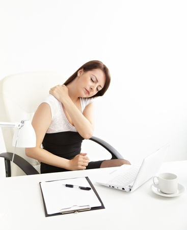 Business woman with back pain after long work on chair photo