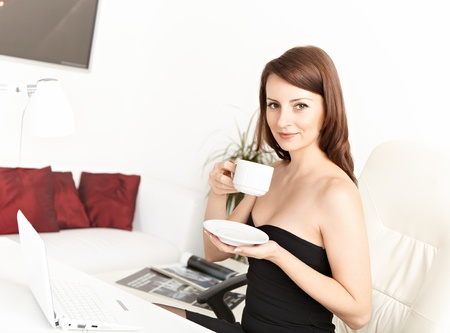 Portrait of a smart young businesswoman drinking coffee at office photo