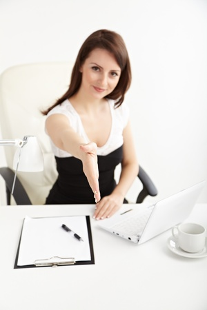 Beautiful  businesswoman greeting  in brightly lit office and smiling photo