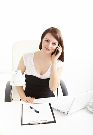 Portrait of a smiling young business woman speaking on mobile phone photo