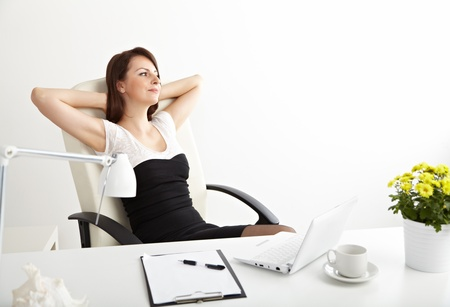 arms behind head: Young  business woman resting at desk in office