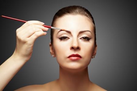 mujer maquillandose: Retrato de mujer atractiva la aplicaci�n de maquillaje sobre un fondo oscuro Foto de archivo