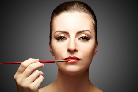 Portrait of attractive woman applying makeup on a dark background Stock Photo - 14509996