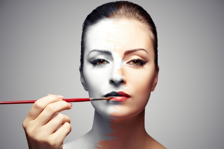 attractive woman paints her  black and white face, bright makeup photo