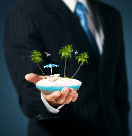Man holds in his hand a tropical island  Stock Photo - 15154573