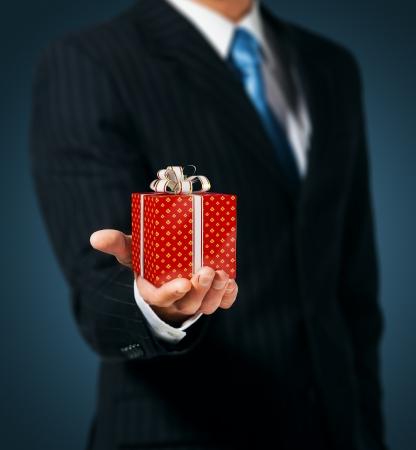 dar un regalo: Hombre que sostiene una caja de regalo