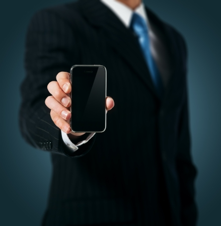 businessman phone: Businessman holding mobile phone Stock Photo