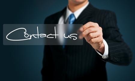contact info: mano d'affari spingendo contattarci pulsante su una interfaccia touch screen