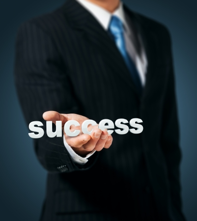 Businessman holds in a hand a word success photo