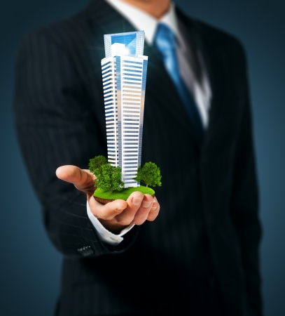 agente comercial: Hombre que sostiene un rascacielos en la mano