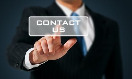 iconos contacto: mano de hombre de negocios empujando contactarnos bot�n en una interfaz de pantalla t�ctil