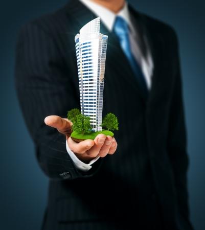 makler: Man h�lt einen Wolkenkratzer in der Hand